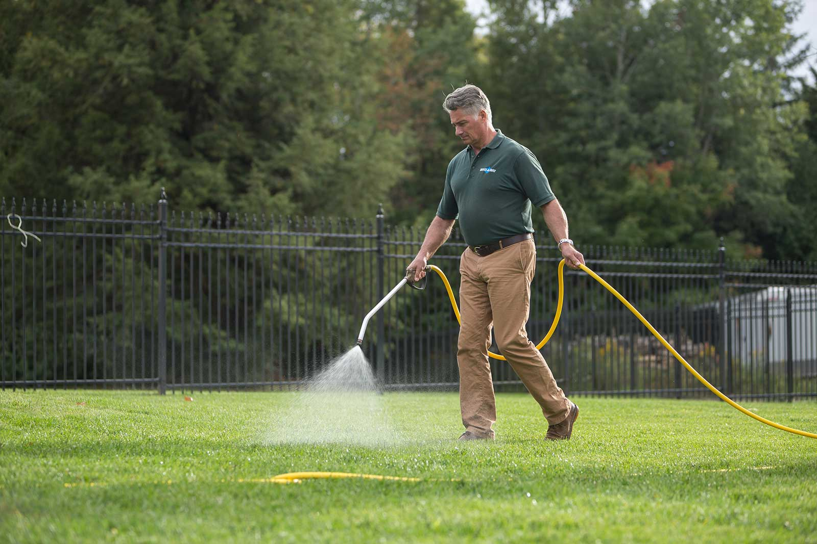 kevin mahoney spraying lawn with hose